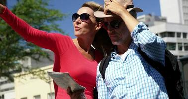 casal maduro está olhando um mapa e apontando
