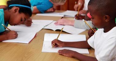 les élèves dessinent dans des blocs-notes pendant la classe