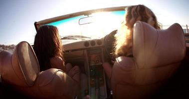 amici hipster seduti in una decappottabile vintage godendosi il tramonto