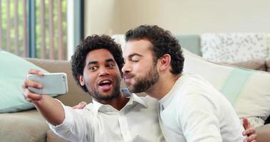 coppia gay rilassante sul divano prendendo selfie video
