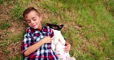 cucciolo che lecca il viso del ragazzino che giace nell'erba