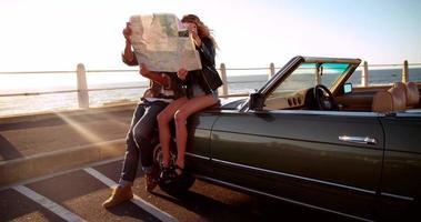 casal hipster procurando mapa em viagem de verão com conversível
