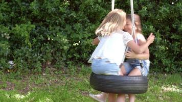 due ragazze che giocano sull'altalena di pneumatici in giardino