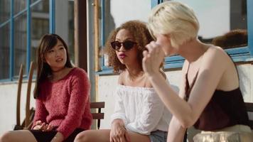 três jovens amigas em um café ao ar livre video