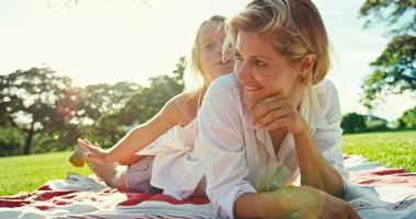 mãe e filha relaxando no parque