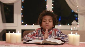 niño afro rezando.