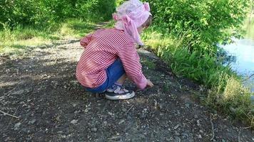 bambina che lancia pietre in acqua di stagno. video