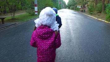 ragazzo biondo e ragazza bambino bambino con gli occhiali divertendosi nel parco giochi nel parco. i bambini piccoli si divertono insieme nel fine settimana.