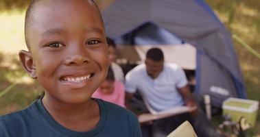 bambino sorride alla telecamera davanti a una tenda video