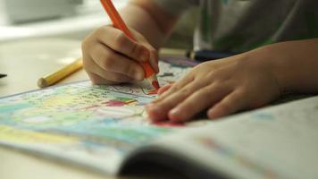 Kinderhände malt einen orangefarbenen Stift auf ein Papier