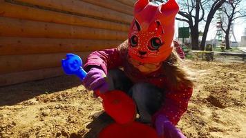 menina criança brincando na caixa de areia. garota posando bolo na areia. video