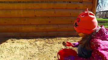 menina criança brincando na caixa de areia. garota posando bolo na areia.