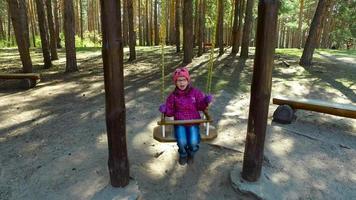 niña niño columpiándose en un columpio en el parque. la niña está feliz y sonriente. video