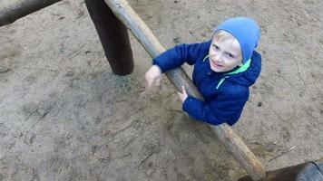 menino criança loira está envolvida nas toras de madeira. menino brincando no playground.