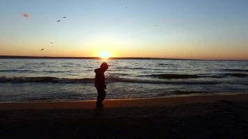 Mädchen geht am Ufer eines großen Sees entlang. Sie rennt am Wasser entlang.