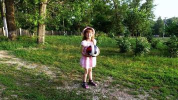 niña jugando a la pelota en el césped. en el rostro de una niña sonriendo de alegría.