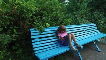 menina de óculos, trabalhando com entusiasmo em um computador tablet. menina se senta em um banco de madeira no parque. video