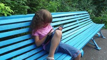 menina de óculos, trabalhando com entusiasmo em um computador tablet. menina se senta em um banco de madeira no parque.