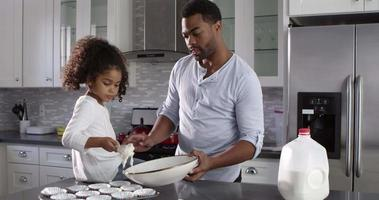 Black dad and young daughter prepare cakes for baking, shot on R3D