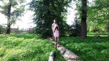 ragazzo adolescente e ragazza bambino che cammina su un registro. fratello e sorella che si aiutano a vicenda a camminare sulla trave di equilibrio.