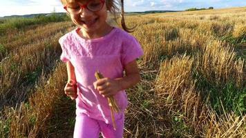 Mädchen läuft über das Feld. Auf dem Feld ist die Weizenernte bereits gesammelt. Die Kamera mit Steadicam bewegt sich hinter dem kleinen Mädchen her