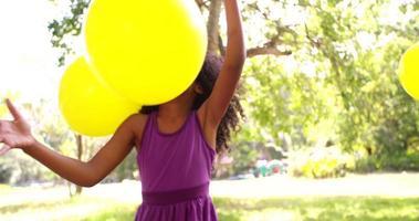ragazza afro cattura felicemente palloncini colorati in un parco