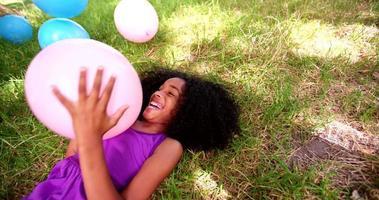ragazza afro sdraiata con palloncini colorati sull'erba