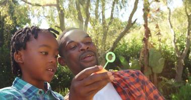 man doet zeepbellen met zijn zoon