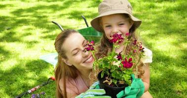 Cute little girl holding pot of flowers with her mother