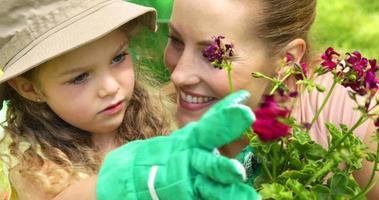linda garota olhando para um vaso de flores com a mãe