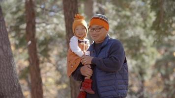 pai carregando criança de sua filha durante uma caminhada em uma floresta video