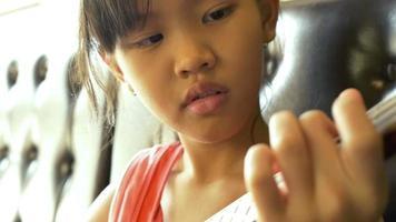 Little Asian child playing ukulele on sofa