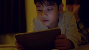 Asian child playing game on mobile phone