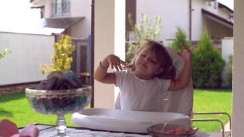 hermoso niño baila y canta a la hora del almuerzo al aire libre