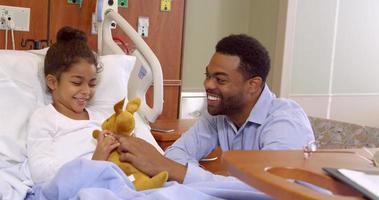 père et enfant jouent avec une peluche à l'hôpital tourné sur r3d