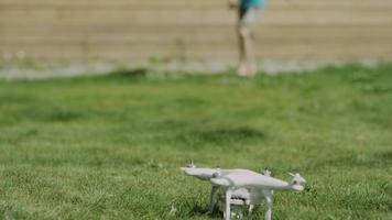 bambino che monta drone moderno sul prato di erba verde. mettere le eliche