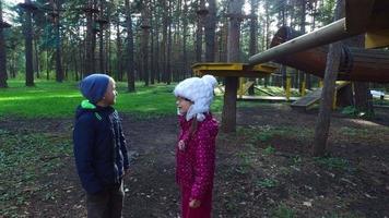 menino criança loira e menina de óculos andando na grama verde. as crianças aprendem uma grande estrutura de escalada.