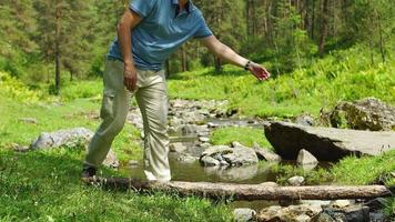 homem ajuda uma criança a atravessar um riacho