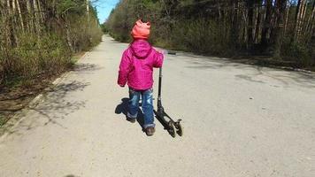 passeggiare nel parco in primavera. ragazza bambino scooter rotola lungo il percorso di asfalto.