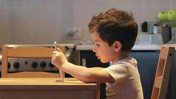 SIDE VIEW: A cute little child uses a tablet PC at a table at home. Clothes: white shirt