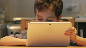 PORTRAIT: A cute little child holds at hands a white tablet PC at a table at home. Casual clothes