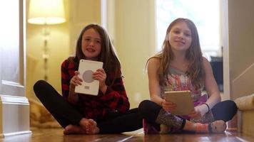 dois amigos sentados juntos no corredor sorrindo e usando seus tablets