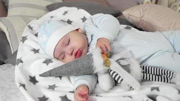 sleeping child, baby sweetly sleep hugging toy, little boy asleep in his parents' house in the winter, cozy atmosphere of winter holidays video