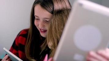amici preadolescenti che usano i loro tablet insieme a casa