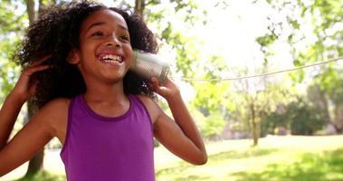 felice ragazza afro ascoltando attentamente un barattolo di latta telefono