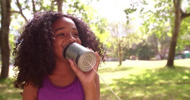 ragazza afro parlando in un barattolo di latta telefono