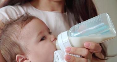 mãe alimentando bebê da mamadeira em casa