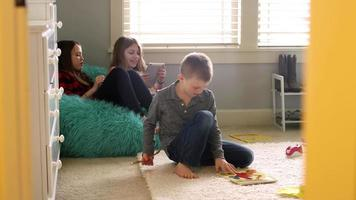 Drei Kinder spielen zu Hause mit Tablets und Origami, Türrahmen im Vordergrund video