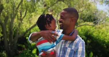 homem abraçando o filho e olhando para a câmera
