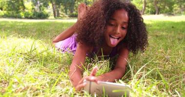 Afro-Mädchen, das für ein Telefon-Selfie in einem Park lächelt video